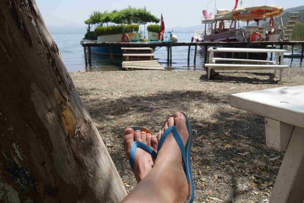 Twee voeten in teenslippers met op de achtergrond Summer garden botanic boat aan de steiger op Jimmy's Beach