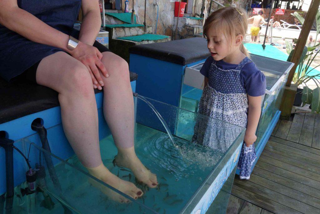 Klein meisje kijkt naar de voeten van haar moeder in een bak met kleine visjes