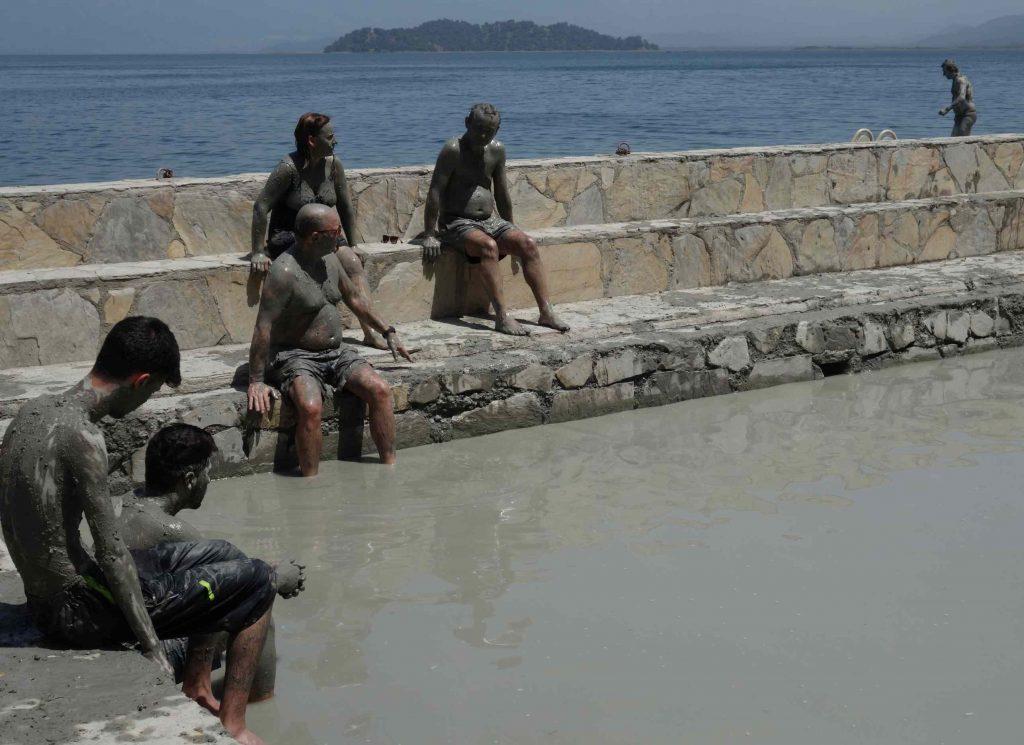 Mensen ingesmeerd met modder drogen op in de zon