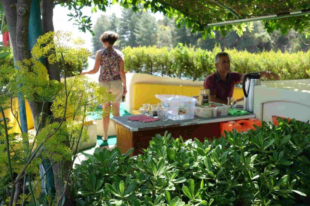 Kapitein Taner Yalili aan het stuur van Summer garden botanic boat met bloemen en planten op voor- en achtergrond
