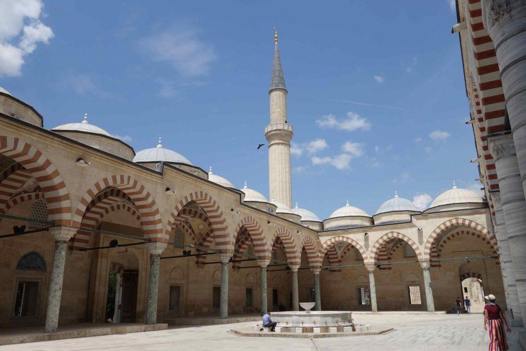 Binnenplaats van de Üç Şerefeli omgeven door bogen en pilaren en een fontein in het midden