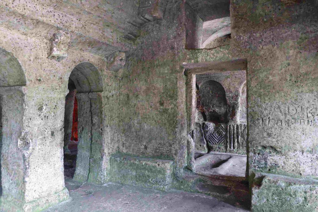 Binnenaanzicht van rotsklooster, doorkijkjes naar verschillende ruimtes en versiering in de rotsen ingekerfd