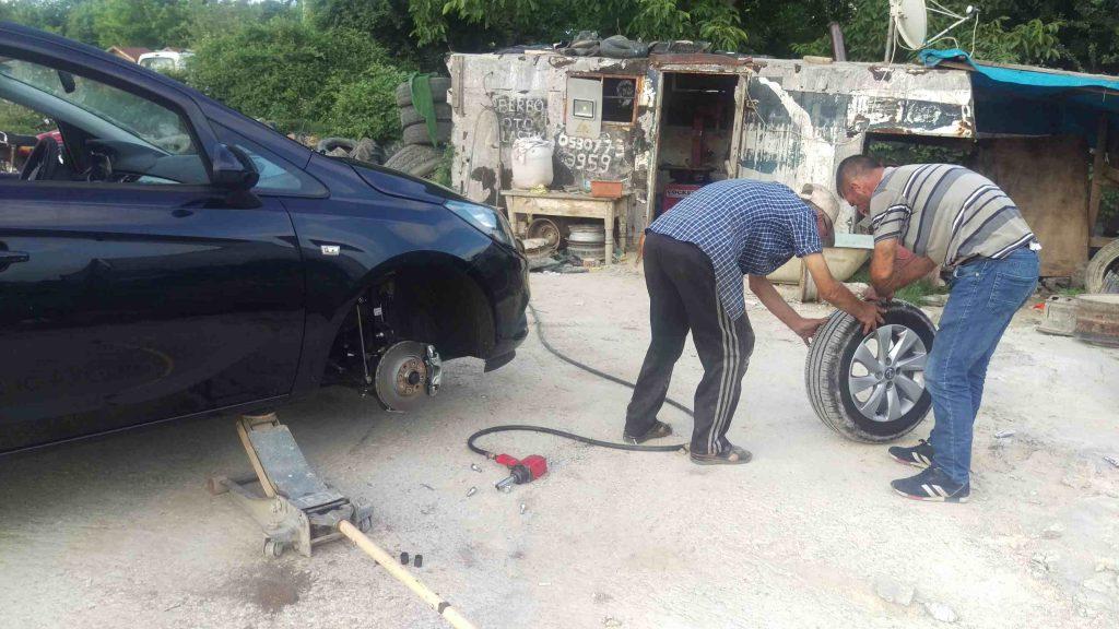 Twee mannen verwisselen een band van een zwarte auto
