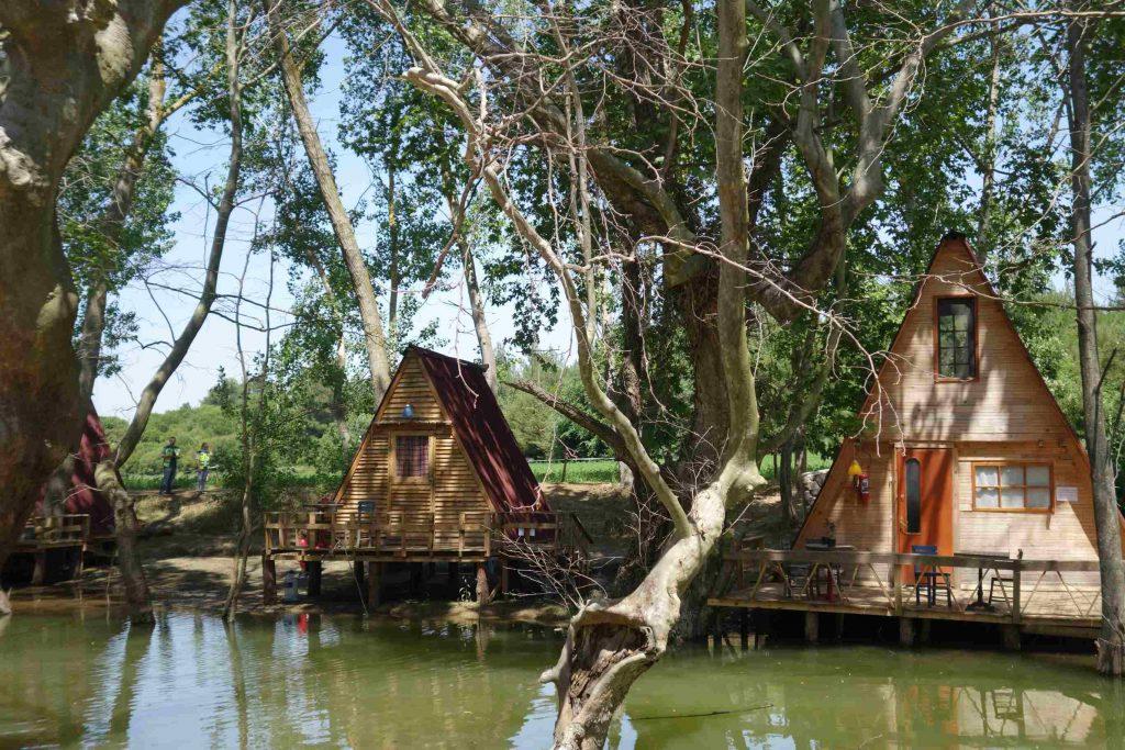 Driehoekige houten huisjes gebouwd op een vlonder boven het water