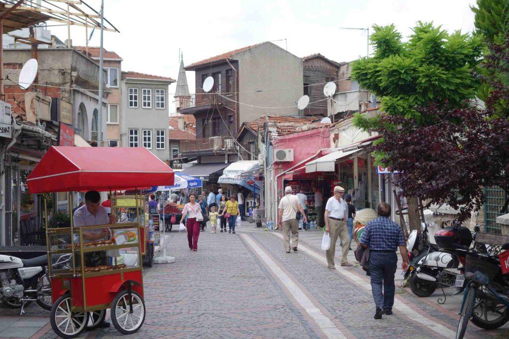 Straatbeeld in Edirne - Thracië, simitverkoper, winkelend publiek en huizen en winkels op de achtergrond