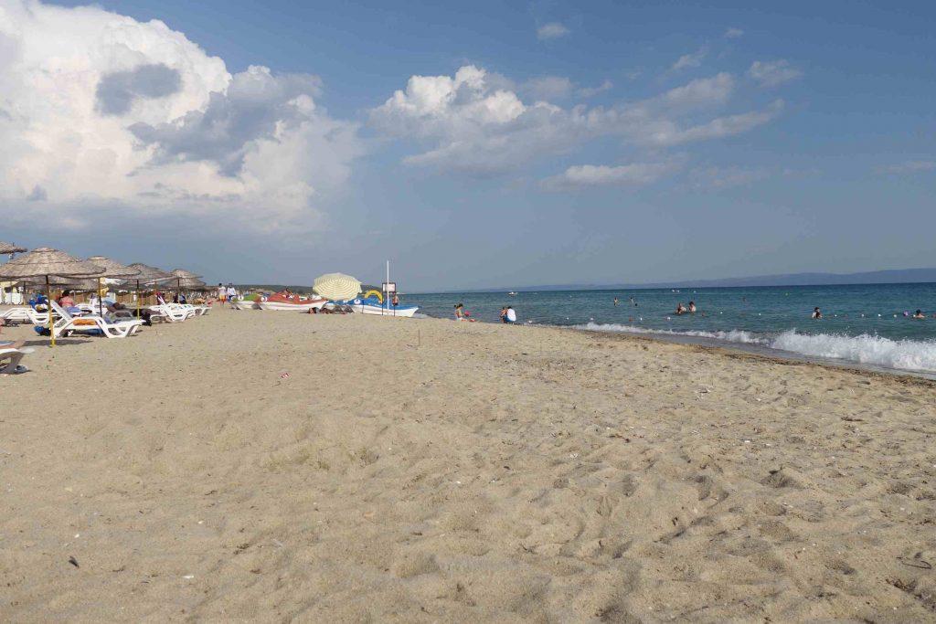 Strand met zee en ligbedjes met parasols