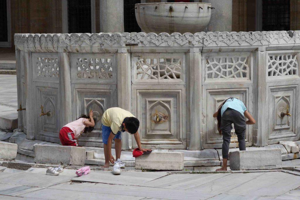 Kinderen wassen zich bij en drinken uit de kraantjes van een moskeefontein