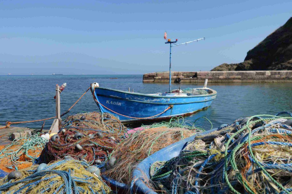 Klein blauw vissersbootje met op de voorgrond een kluwen van gekleurde touwen en visnetten
