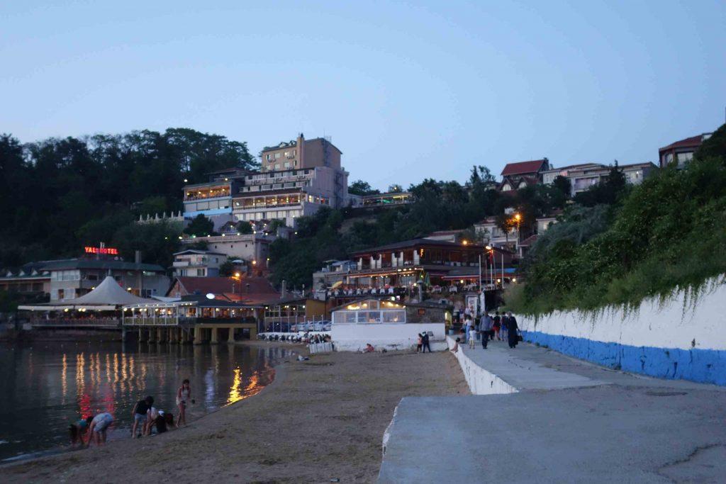 Zicht op Kiliyos vanaf het strand, huizen en hotels tegen de heuvel aan gebouwd en veel groen