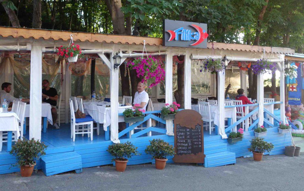 Visrestaurantje met blauw/wit hout, witte stoelen en gekleurde bloemen
