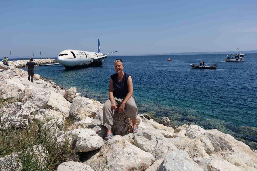 Het karkas van een vliegtuig wordt door bootjes op zee gesleept. Turkeytraveller Margreet zit op de rotsen ervoor.