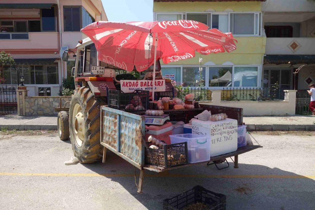 Tractor met aanhanger die helemaal is volgeladen met spullen om op de markt te verkopen. eieren, boter, honing