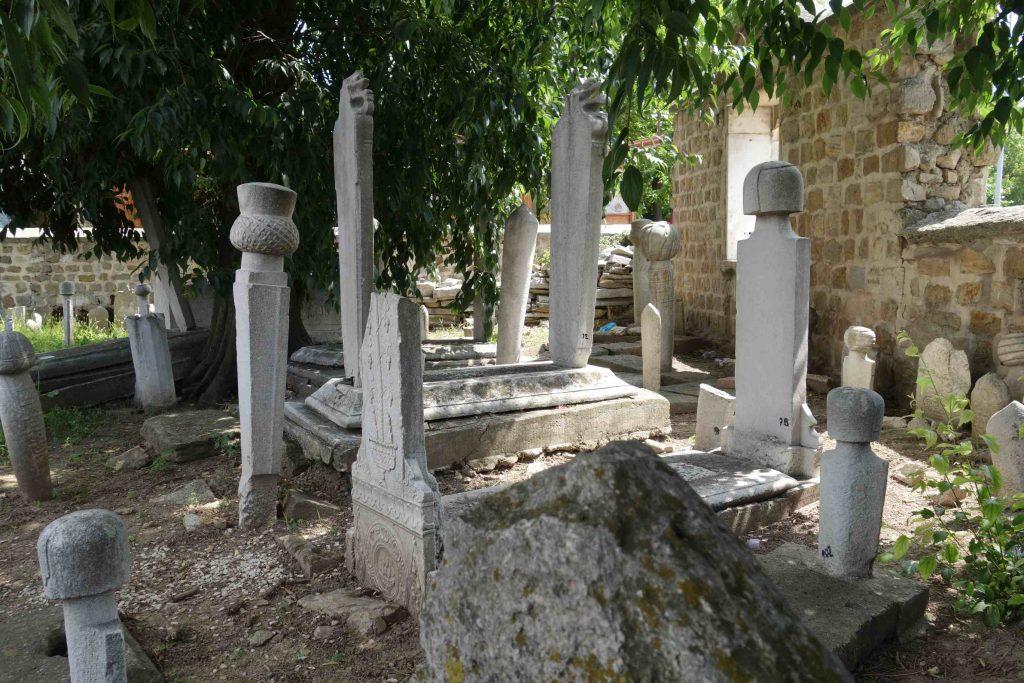 Kris kras door elkaar staande Ottomaanse grafstenen onder een boom met een muur erachter