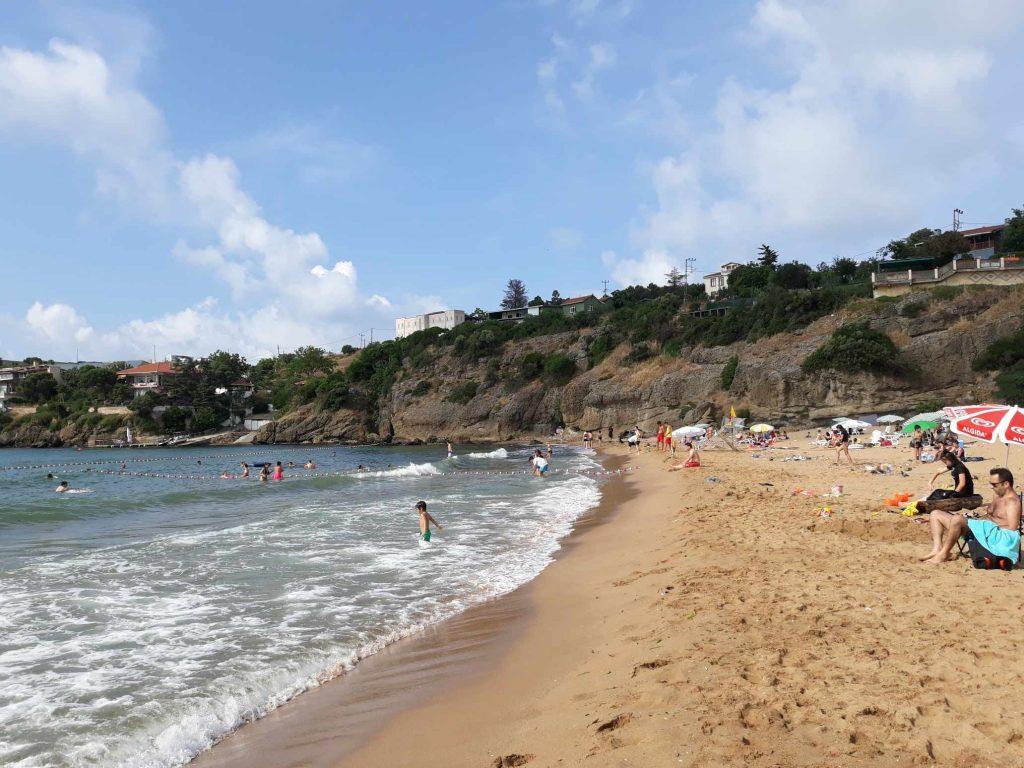 Strand en zee met op de achtergrond lage rotsen waar struiken op groeien en huizen op staan in Riva - Thracië