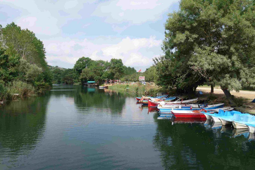 Rivier met groene oevers waar bootjes en waterfietsen aangemeerd liggen