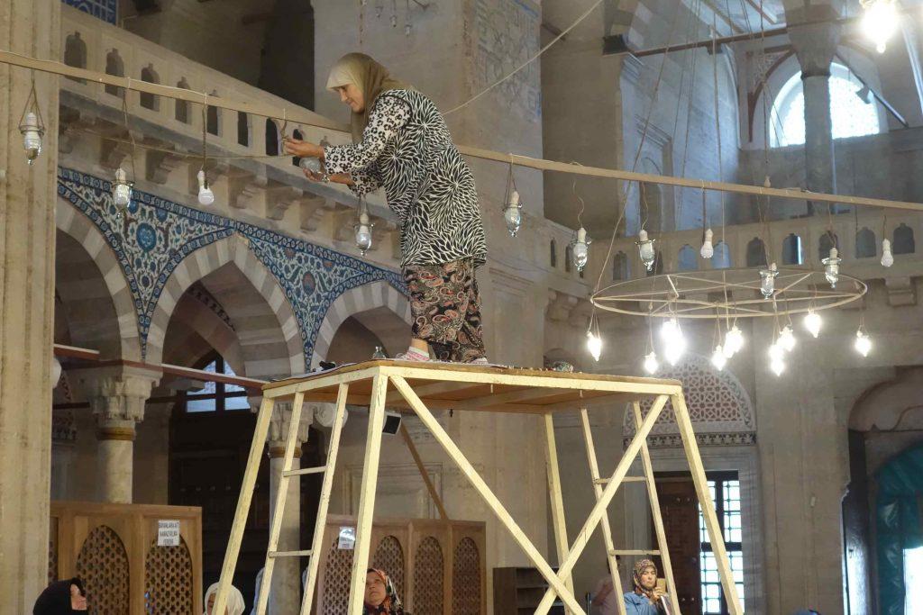Vrouw met hoofddoek op stellage vervangt lampen in een moskee