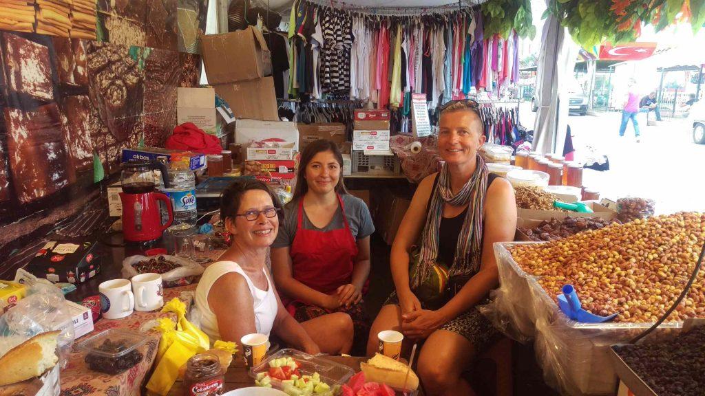 Drie dames poseren zittend in de notenkraam op de markt
