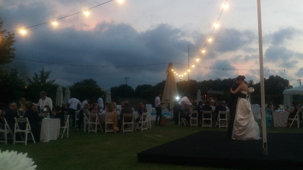 Bruidspaar danst op podium, eromheen mensen die aan tafels zitten te eten