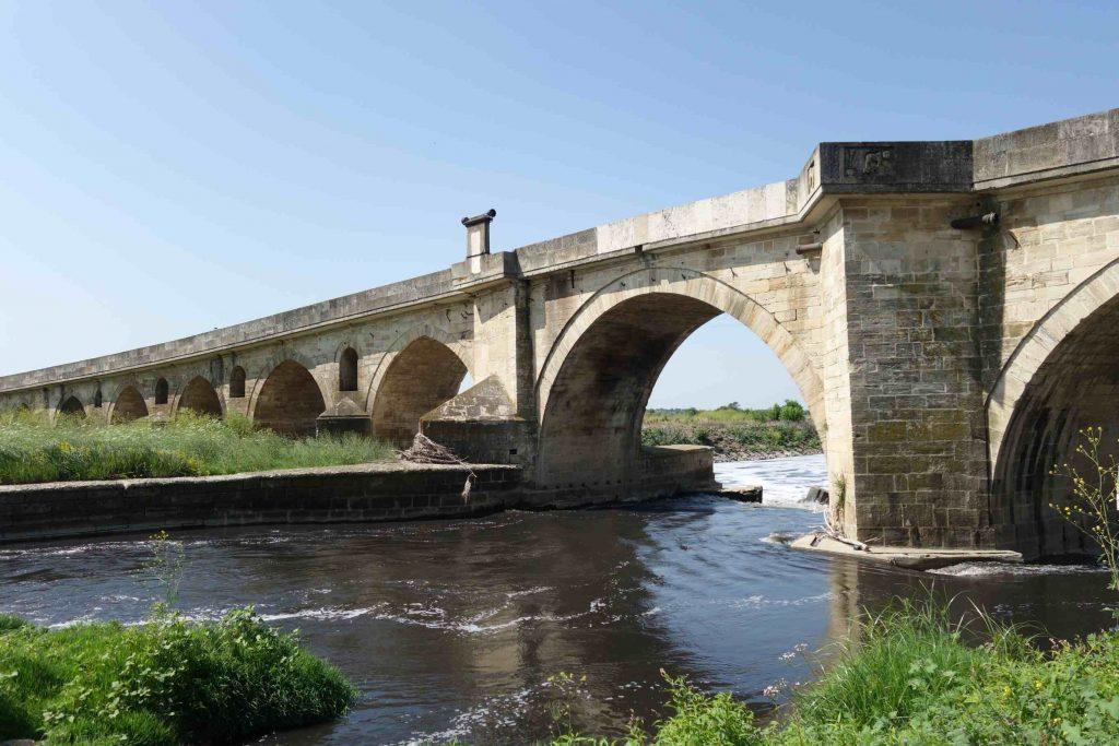 Oude stenen boogbrug met daaronder de rivier