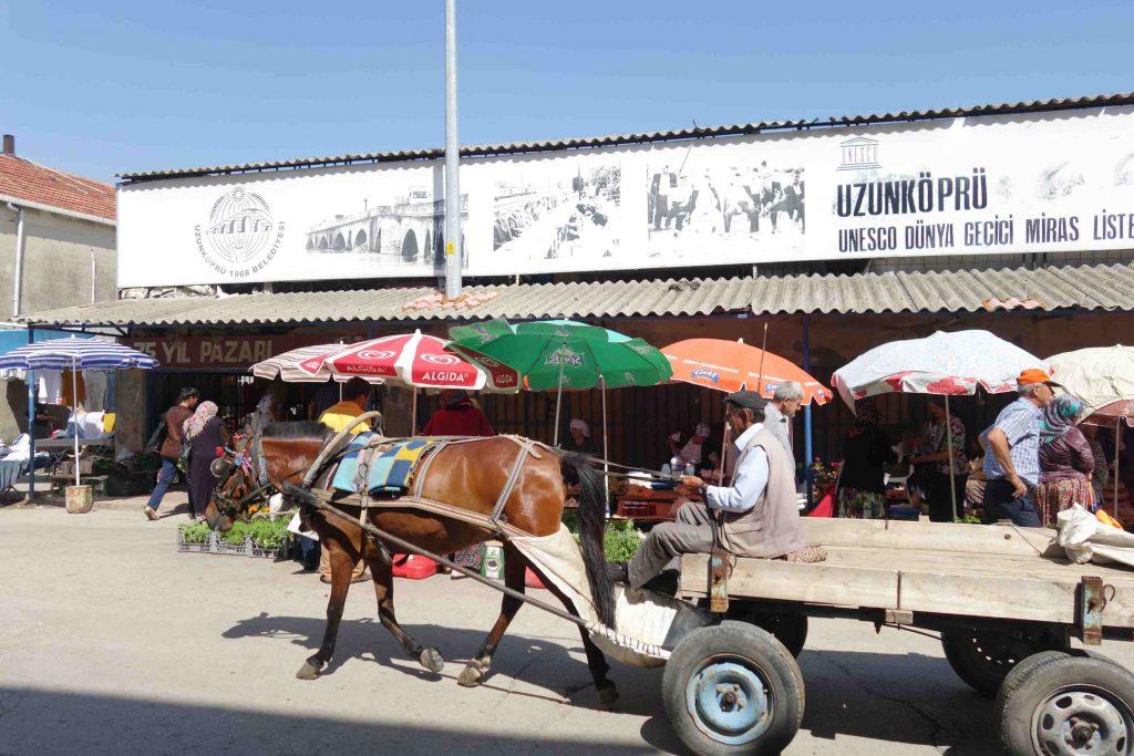 Man met paard en wagen die voor een overdekte markthal in Uzunköprü - Thracië langs rijdt