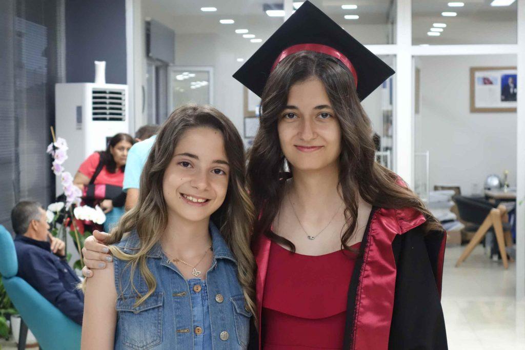 Twee lachende Turkse meisjes, een in toga met bijpassen hoofddeksel voor diploma-uitreiking
