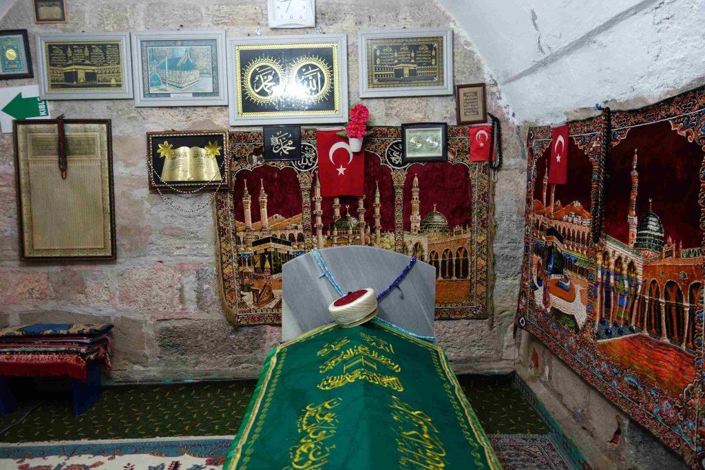Graf van Turkse heilige in een grafkamer met tapijten en andere Turkse decoraties aan de muur