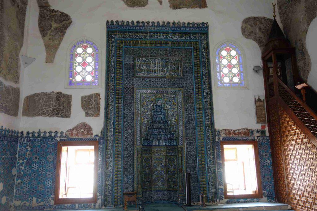 Een muur van de Muradiye moskee, bekleed met tegels in allerlei kleuren blauw en daarboven Ottomaanse inscripties