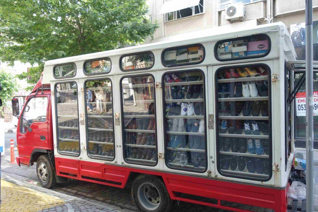 Vrachtauto met glazen zijkanten met daarachter allerlei verschillende schoenen te koop