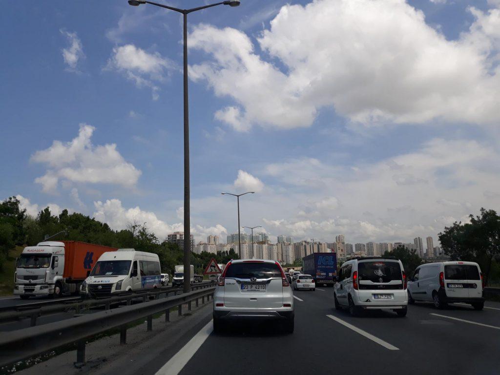 3 rijen auto's op de ringweg van Istanbul met in de verte de torenflats van de stad