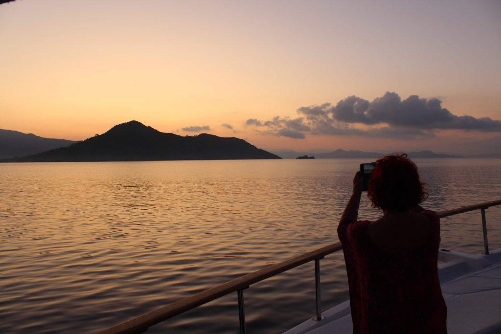 Passagier aan boord van een Turks zeilschip maakt met telefoon een foto van zonsopgang
