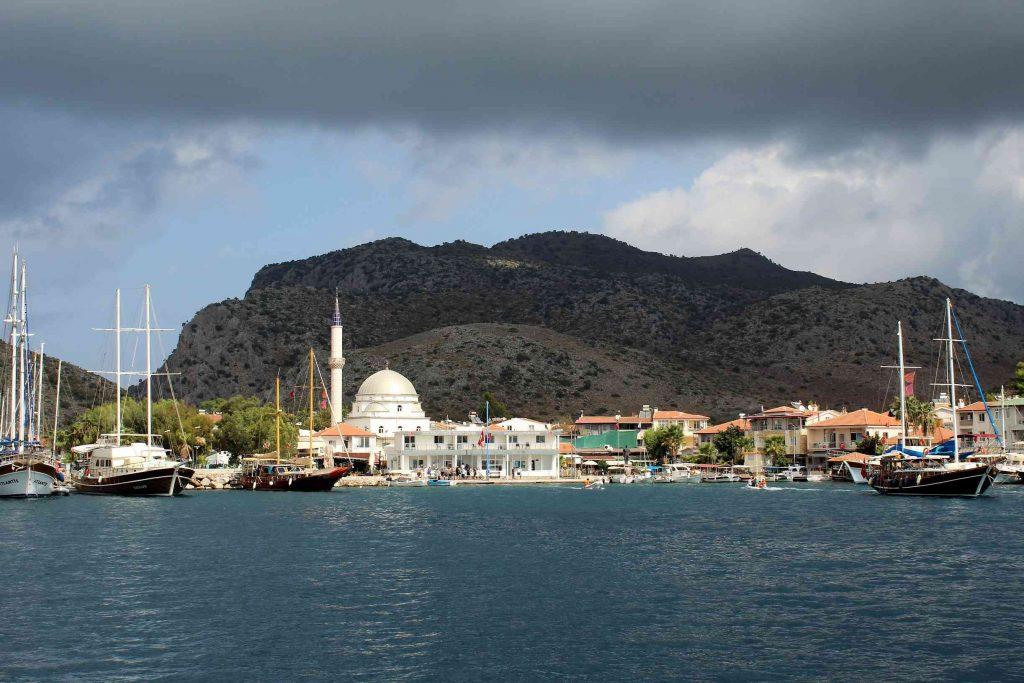 Bozburun in Turkije vanaf het water gezien met enkele zeilschepen op de voorgrond
