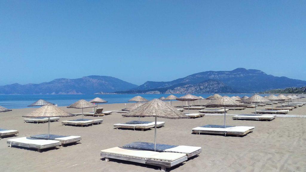 Iztuzu strand bij Dalyan met rijen lege strandbedjes en rieten parasols