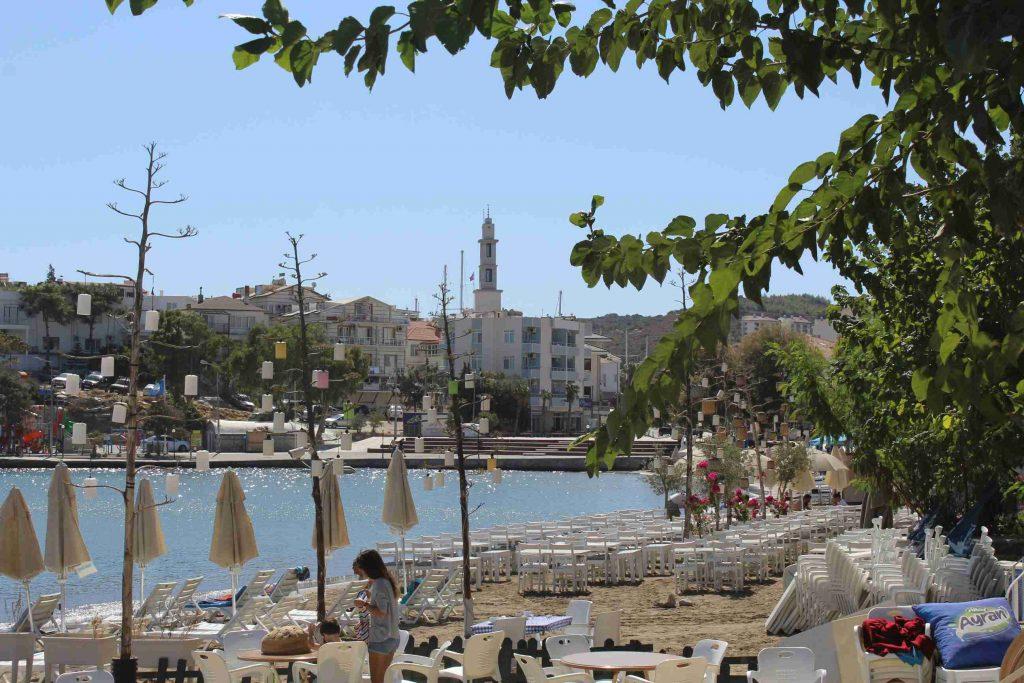 Datça in Turkije, het strand met zonnebedjes en terrassen op het strand en het dorp op de achtergond