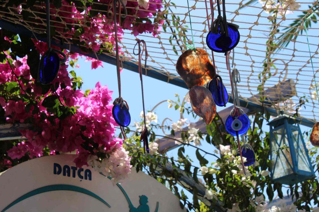 Stilleven van Turkse blauwe ogen met schelpen die hangen aan een visnet met bloeiende roze en witte bloemen eromheen