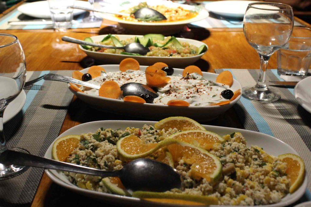 Drie verschillende soorten salades met garnering op een gedekte tafel