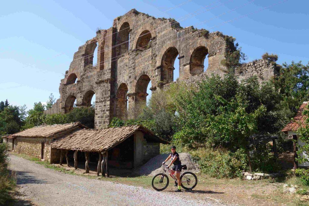 Vrouwelijke fietser poseert voor Aspendos aquaduct in Turkije