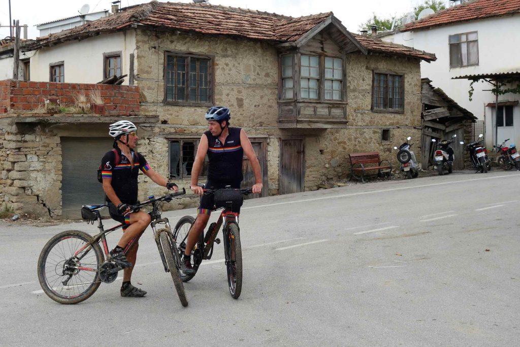 Twee fietsers in zwart tenue staan met mountainbike in Turks dorp met op de achtergrond een vervallen Ottomaans huis