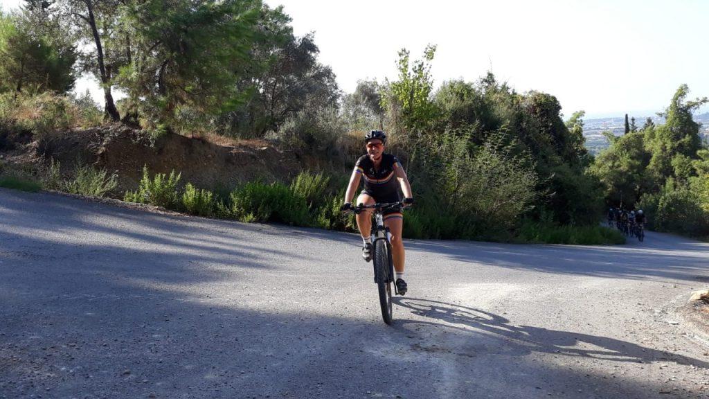 Vrouwelijke fietser klimt tegen een heuvel op met op de achtergrond nog een groep fietsers in Turkije
