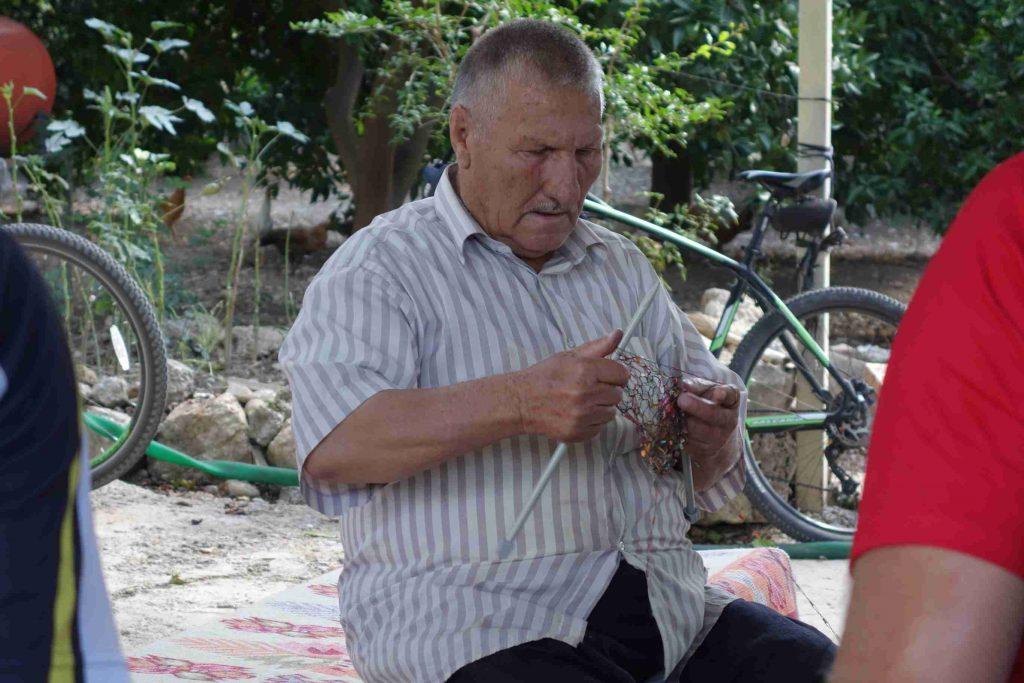 Turkse man breit een sjaal en kijkt ingespannen naar zijn breiwerk