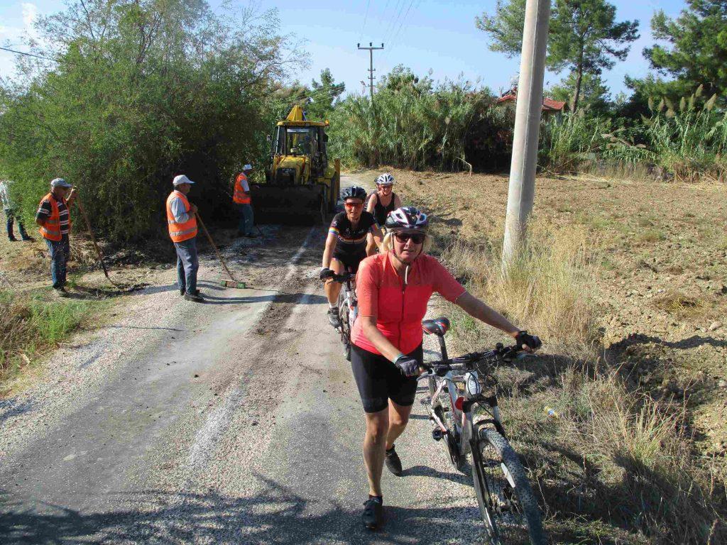 Drie dames op de fiets in Turkije, eentje loopt en op de achtergrond een bulldozer die aan de weg bezig is