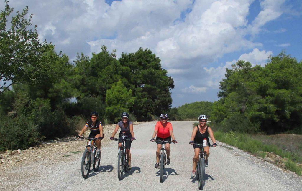 Vier dames fietsen in Turkije naast elkaar op een weg met groene struiken en bomen aan weerszijden