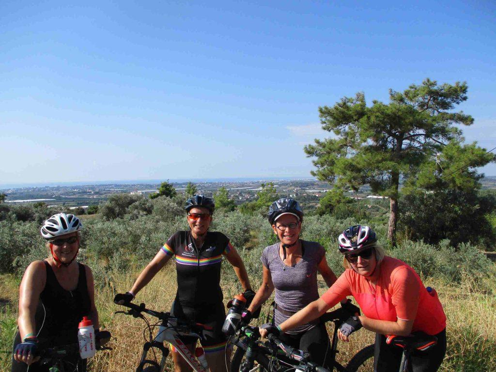 Vier dames in fietskleding en met mountainbikes poseren met op de achtergrond Side en de Middellandse Zee