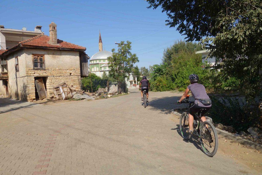 Fietsen in Turkije door een dorpje met een vervallen huis links en recht voor de moskee