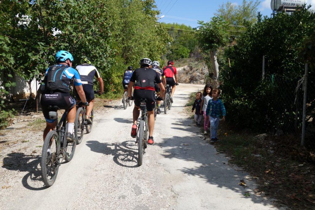Groep fietsers in Turkije passeert drie kleine Turkse kinderen op een pad
