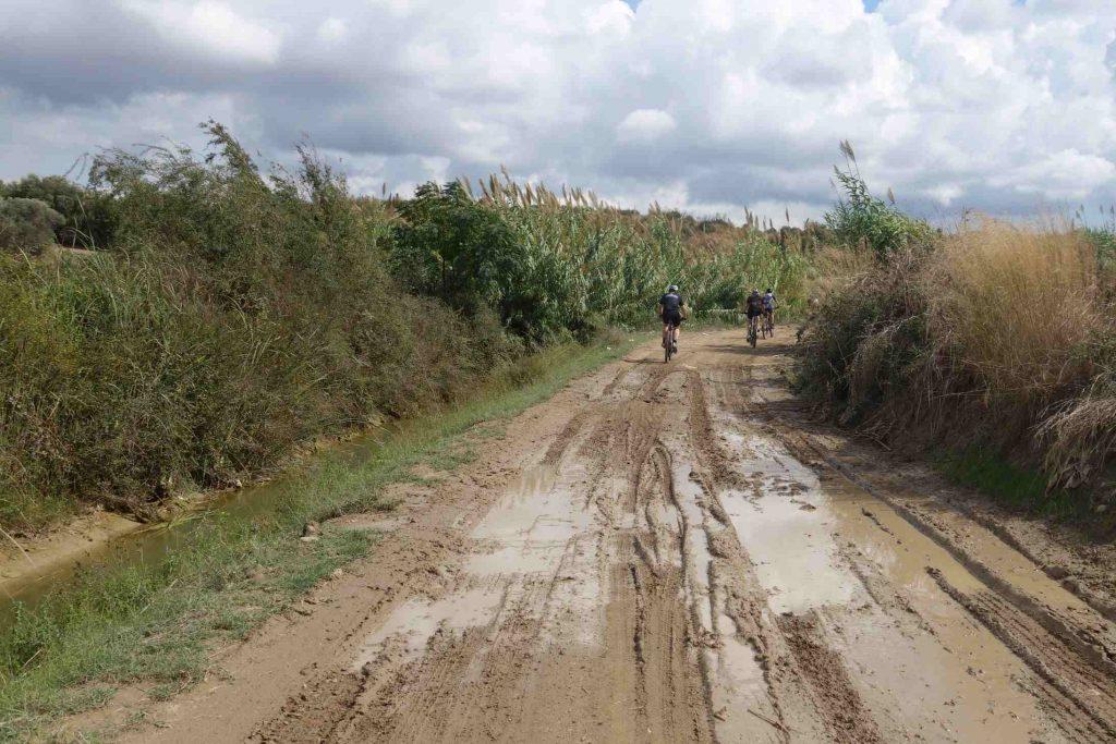 Modderig pad in Turkije met wielsporen en grote plassen en in de verte enkele fietsers
