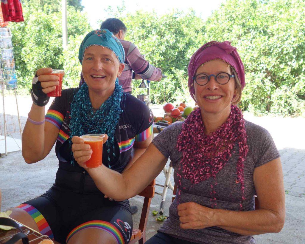 Twee dames in fietskleding met een Turkse sjaal om proosten met een glas vruchtensap