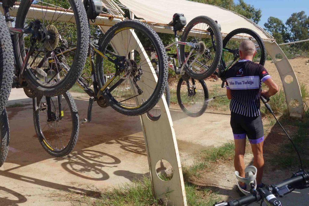 Man in wielertenue reinigt moutainbikes met een hogedrukspuit