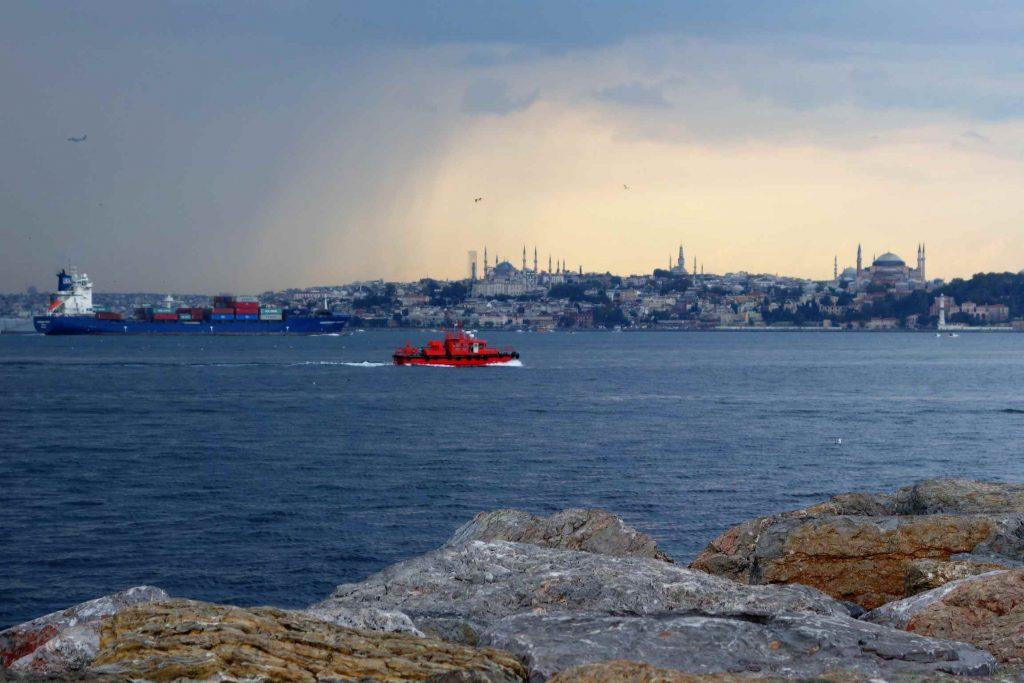 De skyline van Europees Istanbul met grijzen wolkenlucht daarboven en schepen die over de Bosporus varen
