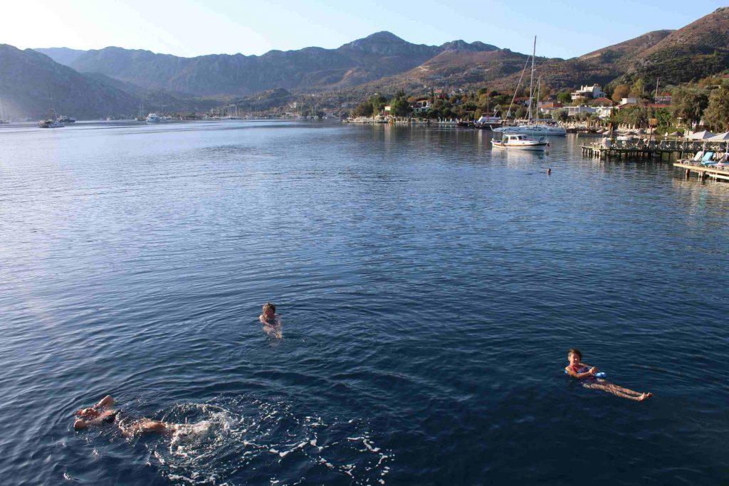 Mensen zwemmen in een baai met op de achtergrond Selimiye in Turkije