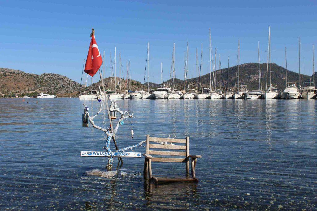 De jachthaven van Selimiye met een stoel die in het water staat en een Turkse vlag ernaast